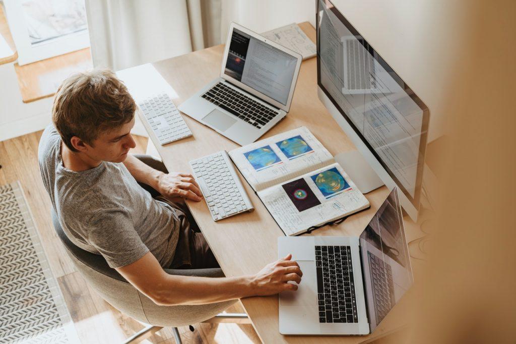 personne assise devant trois écrans d'ordinateur